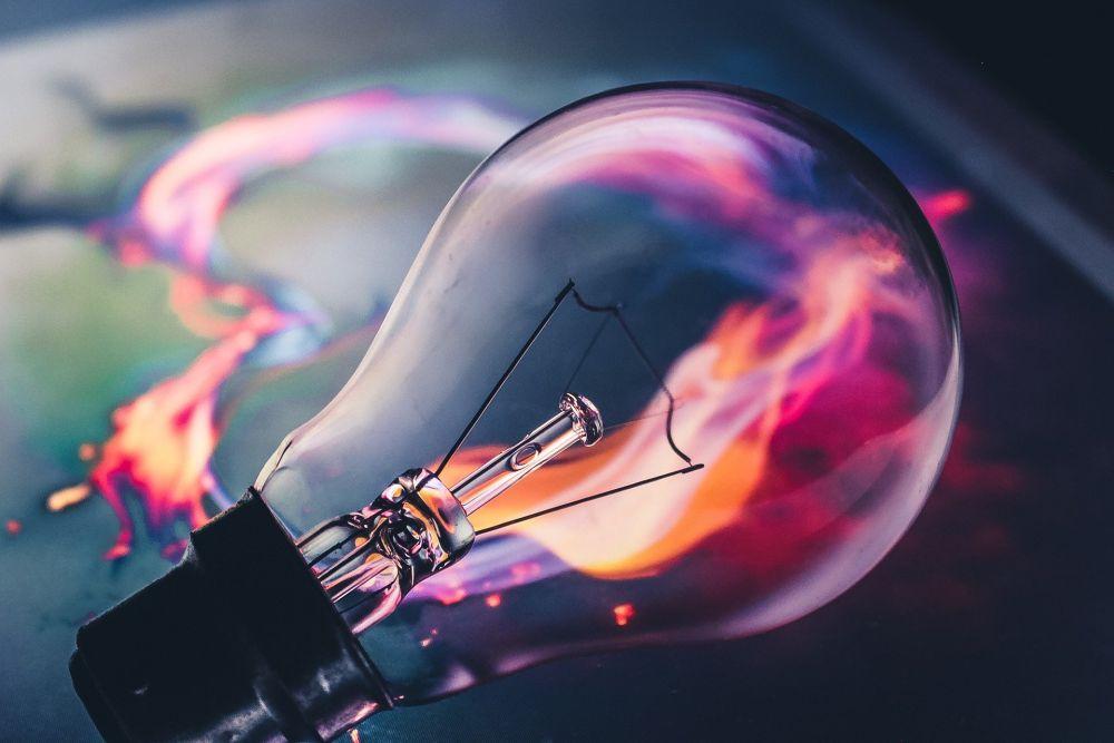 Symbolbild für den Begriff Bildung: Eine Glühbirne, die mit Ideen durchströmt wird