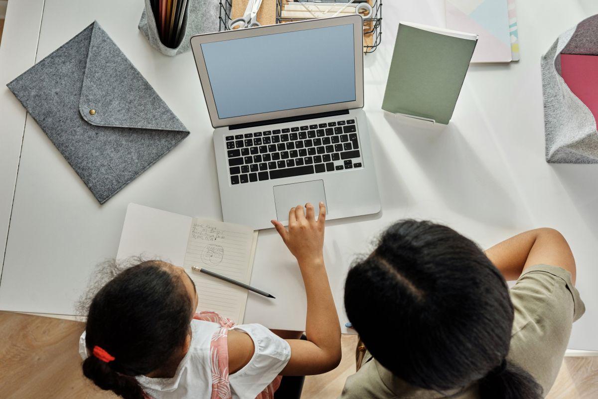 Internet-Suchen: Eine Mutter sitzt mit ihrem Kind vor einem Notebook